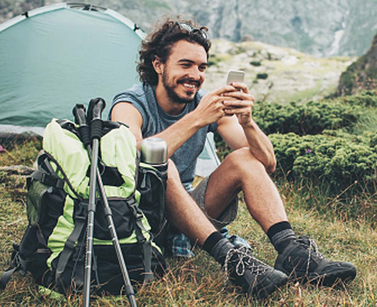 A man checking his MeMail email account on his phone while camping in the mountains.