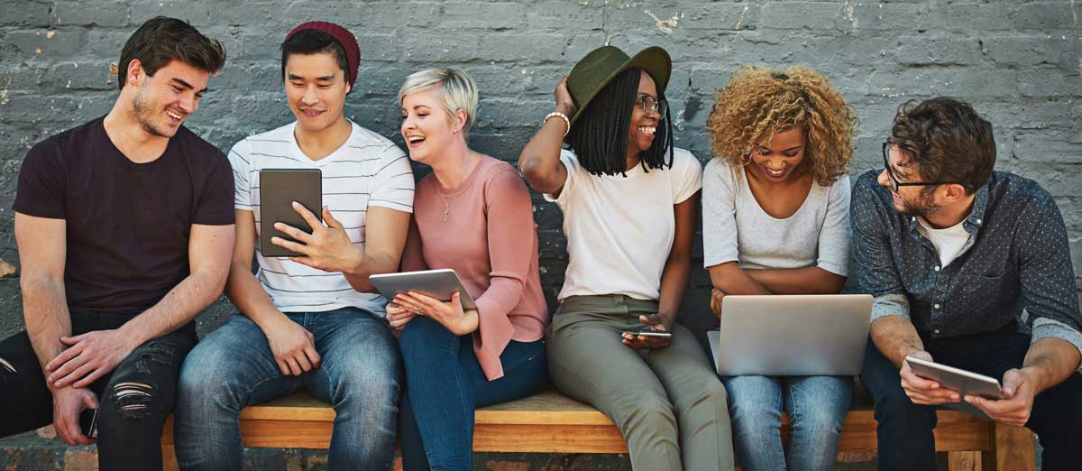 A diverse group of young adults using their favorite mobile devices and checking their MeMail accounts.
